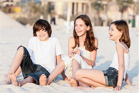 Siblings sitting together on sand at the beach Stock Photo - Premium Royalty-Free, Code: 632-07539954