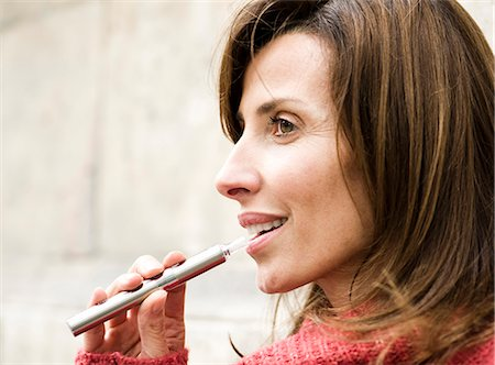 Woman smoking electronic cigarette, profile Stock Photo - Premium Royalty-Free, Code: 632-07539962