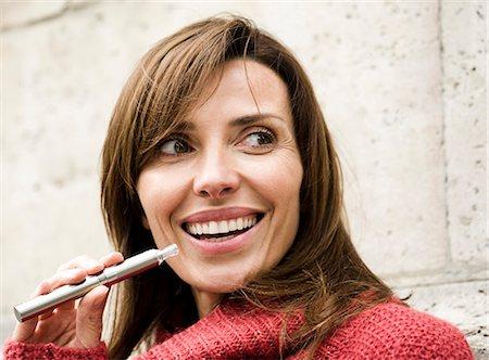 Woman smoking electronic cigarette, smiling Stock Photo - Premium Royalty-Free, Code: 632-07539963
