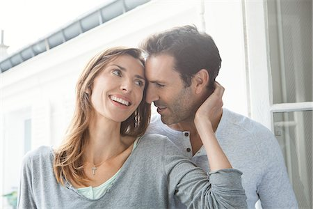 Couple whispering and smiling by window Stock Photo - Premium Royalty-Free, Code: 632-07674436