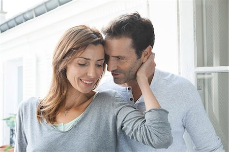 Couple embracing by open window Stock Photo - Premium Royalty-Free, Code: 632-07674437