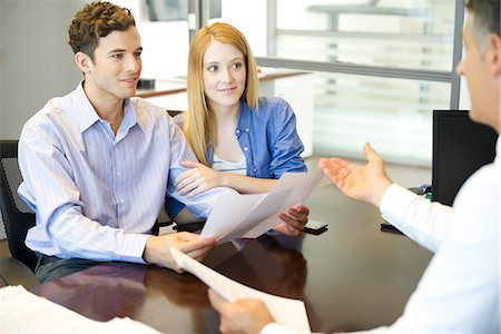 Couple discussing paperwork with advisor Stock Photo - Premium Royalty-Free, Code: 632-07674476