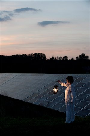 Girl standing in front of solar panels at twilight with old-fashioned lantern in hand Photographie de stock - Premium Libres de Droits, Code: 632-07674478