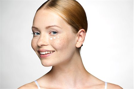 smiling - Young woman applying undereye cream Stock Photo - Premium Royalty-Free, Code: 632-07674608