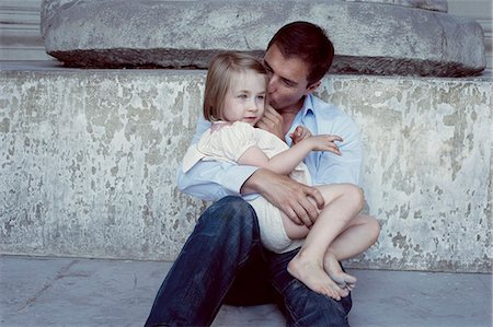 Father holding young daughter on his lap Stock Photo - Premium Royalty-Free, Code: 632-07674648