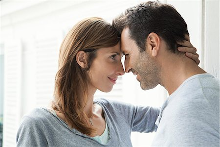 Couple touching noses by window Stock Photo - Premium Royalty-Free, Code: 632-07674657