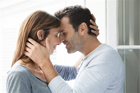 Couple cuddling by open window Stock Photo - Premium Royalty-Free, Code: 632-07674658