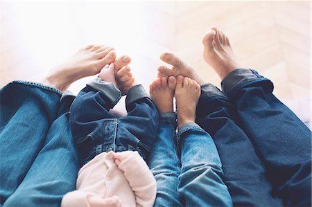 Outstretched legs and barefeet of family with two children Stock Photo - Premium Royalty-Free, Code: 632-07674682