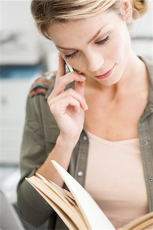 Woman using cell phone while reading book Stock Photo - Premium Royalty-Free, Code: 632-07674693
