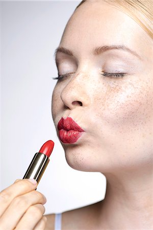 pucker - Young woman putting on lipstick Stock Photo - Premium Royalty-Free, Code: 632-07674755