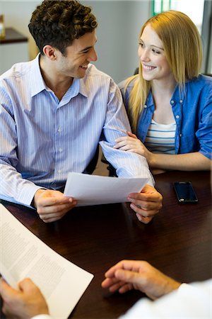 Couple reviewing paperwork in meeting with advisor Stock Photo - Premium Royalty-Free, Code: 632-07674770