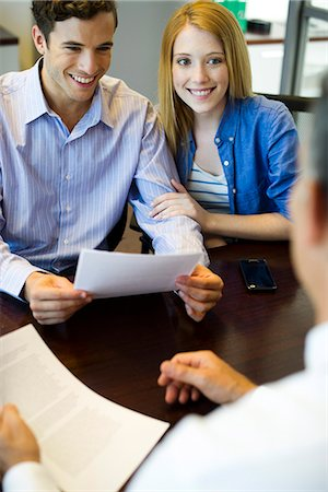 Couple reviewing paperwork in meeting with advisor Stock Photo - Premium Royalty-Free, Code: 632-07674771