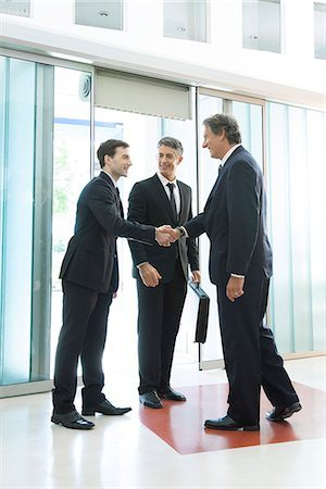 Businessman meeting associates in office lobby Stock Photo - Premium Royalty-Free, Code: 632-07809318