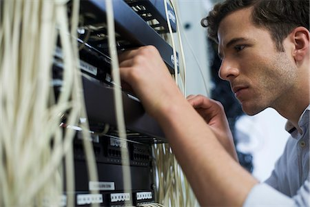 Computer technician performing maintenance on computer networking equipment Stock Photo - Premium Royalty-Free, Code: 632-07809331