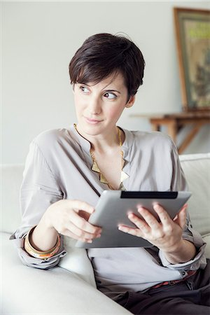Woman using digital tablet at home Stock Photo - Premium Royalty-Free, Code: 632-07809510