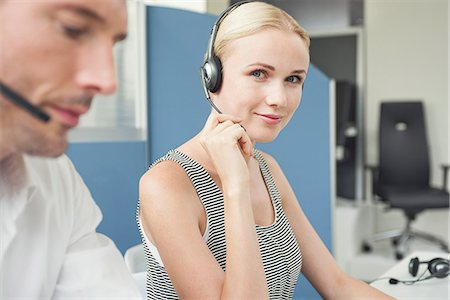 Woman wearing phone headset at desk Stock Photo - Premium Royalty-Free, Code: 632-08001751