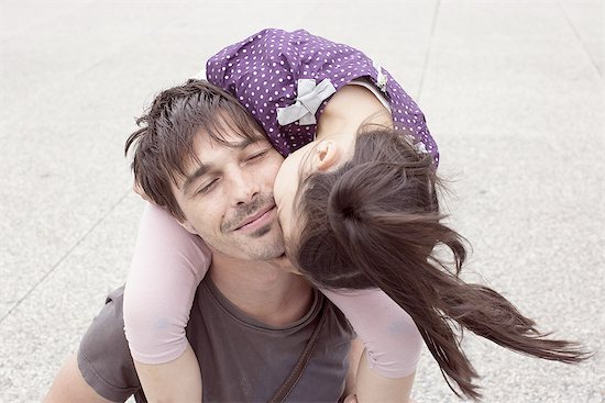 Little girl riding on father's shoulders, kissing his cheek Stock Photo - Premium Royalty-Free, Image code: 632-08001775