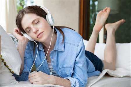 Young woma lying on stomach, listening to headphones with eyes closed Stock Photo - Premium Royalty-Free, Code: 632-08001810