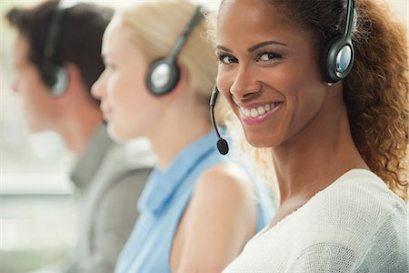 Woman working in call center, smiling cheerfully Stock Photo - Premium Royalty-Free, Code: 632-08001864