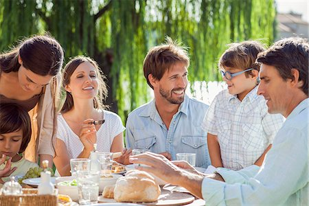 family table eating together - Family enjoying breakfast together outdoors Stock Photo - Premium Royalty-Free, Code: 632-08129729