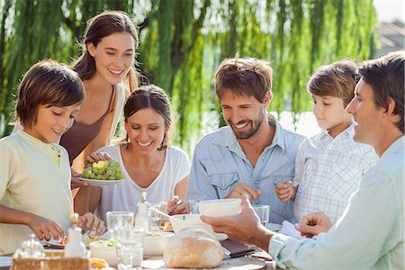 family table eating together - Family enjoying breakfast together outdoors Stock Photo - Premium Royalty-Free, Code: 632-08129730