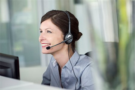 switchboard operator - Receptionist wearing headset, smiling cheerfully Stock Photo - Premium Royalty-Free, Code: 632-08129778