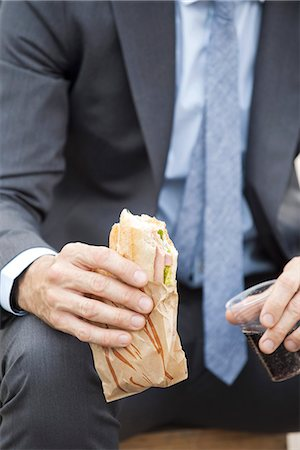 sandwich wrapper - Businessman holding sandwich, cropped Stock Photo - Premium Royalty-Free, Code: 632-08227482