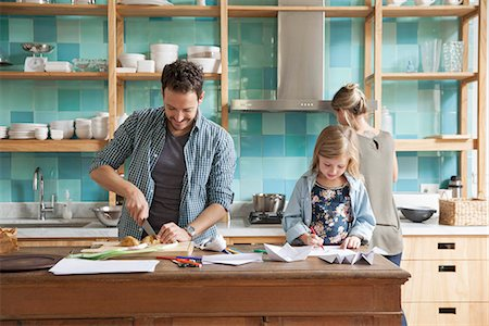 front - Young daughter drawing ar kitchen counter while parents prepare meal Stock Photo - Premium Royalty-Free, Code: 632-08227548