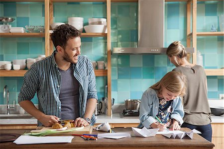 Young daughter drawing ar kitchen counter while parents prepare meal Stock Photo - Premium Royalty-Free, Code: 632-08227550