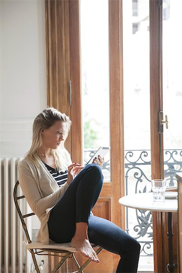 Young woman using digital tablet at home Stock Photo - Premium Royalty-Free, Image code: 632-08227624