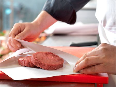 paper - Butcher wrapping beef patties in wax paper, cropped Stock Photo - Premium Royalty-Free, Code: 632-08227686