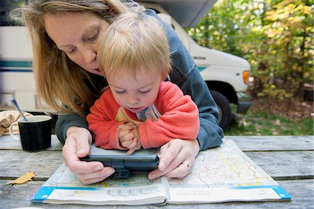 Mother holding child on lap while using atlas and GPS to plan road trip Stock Photo - Premium Royalty-Free, Code: 632-08227814