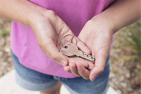 Girl holding key in cupped hands, cropped Stock Photo - Premium Royalty-Free, Code: 632-08331454