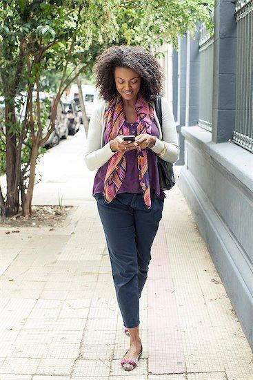 Woman text messaging while walking on sidewalk Stock Photo - Premium Royalty-Free, Image code: 632-08331649
