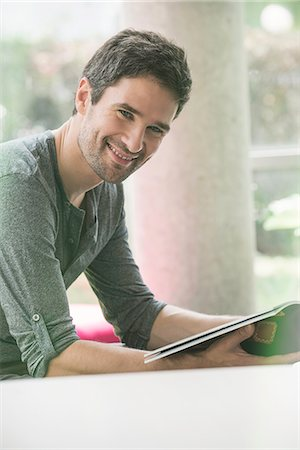 Man looking through magazine while waiting in waiting room Stock Photo - Premium Royalty-Free, Code: 632-08545850
