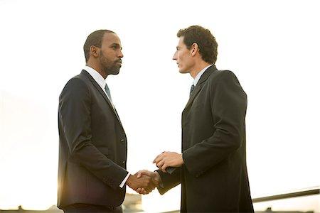 Businessmen shaking hands outdoors Stock Photo - Premium Royalty-Free, Code: 632-08698429
