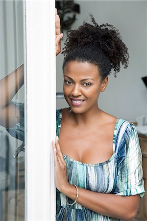 Woman leaning in doorway, smiling, portrait Stock Photo - Premium Royalty-Free, Code: 632-08698496