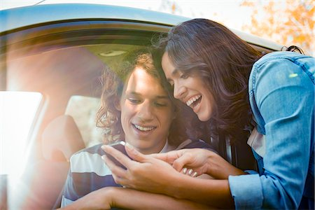 Couple looking for directions on smartphone before embarking on road trip Stock Photo - Premium Royalty-Free, Code: 632-08886479