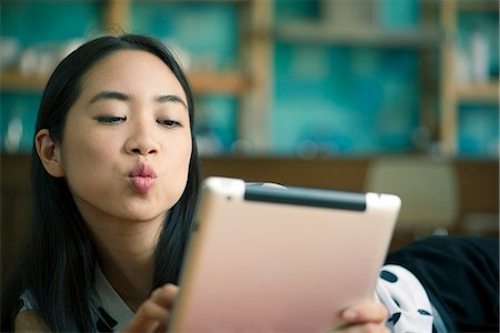 Young woman blowing kiss while video conferencing on digital tablet Stock Photo - Premium Royalty-Free, Code: 632-08886597