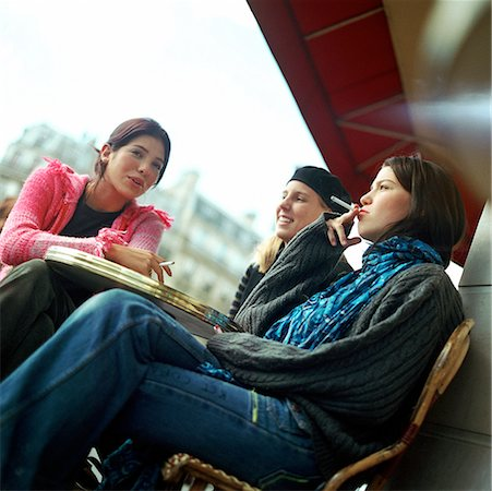 Three teenage girls sitting at cafe terrace, smoking cigarettes, low angle view Stock Photo - Premium Royalty-Free, Code: 632-01137069