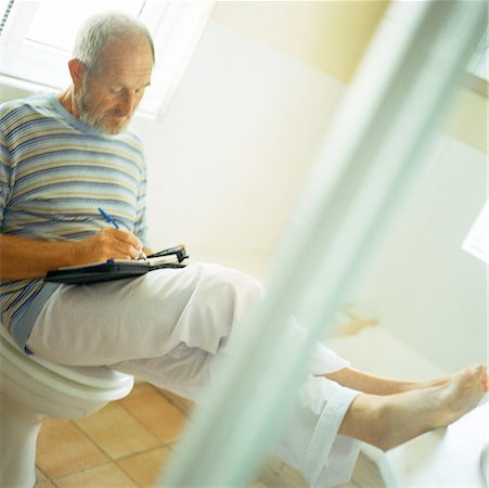 Man sitting on toilet, writing with feet up Stock Photo - Premium Royalty-Free, Code: 632-01144246