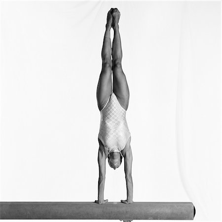 Young female gymnast performing handstand on balance beam Stock Photo - Premium Royalty-Free, Code: 632-01145008