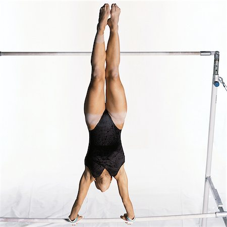 Young female gymnast swinging on uneven bars Stock Photo - Premium Royalty-Free, Code: 632-01145042