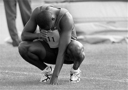 Male athlete crouching, head down, b&w Stock Photo - Premium Royalty-Free, Code: 632-01145066