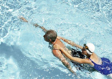 seniors and swim cap - Mature couple swimming in pool, elevated view Stock Photo - Premium Royalty-Free, Code: 632-01146636