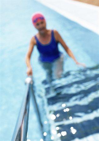 seniors and swim cap - Mature woman in swimming pool, walking up ladder, blurred Stock Photo - Premium Royalty-Free, Code: 632-01146641
