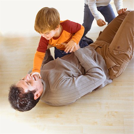Children playing with father on the floor Stock Photo - Premium Royalty-Free, Code: 632-01147934
