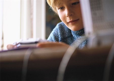 preteen  smile  one  alone - Young boy looking at video game, close up, computer and desk blurred in foreground Stock Photo - Premium Royalty-Free, Code: 632-01149439