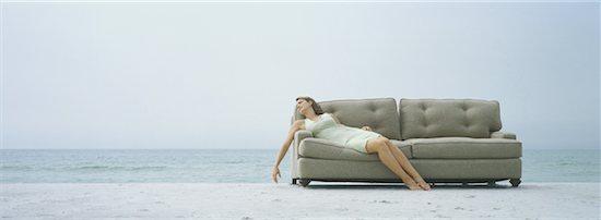 Woman reclining on sofa, on beach Stock Photo - Premium Royalty-Free, Image code: 632-01156092