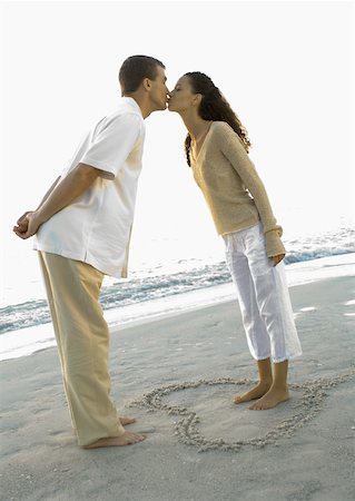Newlyweds, woman standing inside heart drawn in sand, leaning forward to kiss husband Stock Photo - Premium Royalty-Free, Code: 632-01156247